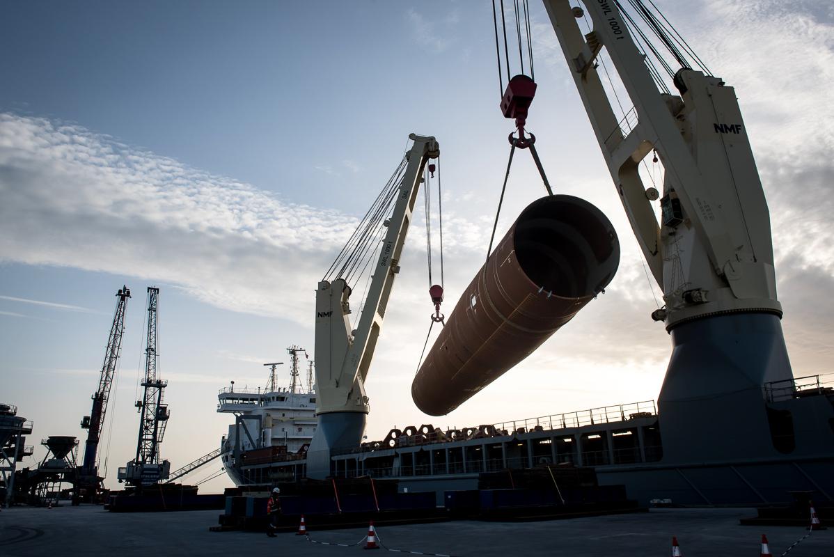 Vue en contre-jour du déchargement d'un monopied d'une éolienne au port maritime de la Rochelle